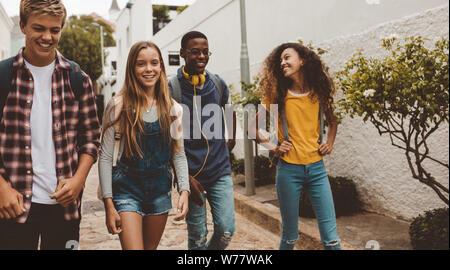 Collège multiethnique amis marchant dans la rue. Heureux les garçons et les filles de la rue à pied portant des sacs de collège. Banque D'Images
