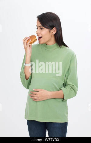 Pregnant woman eating hamburger