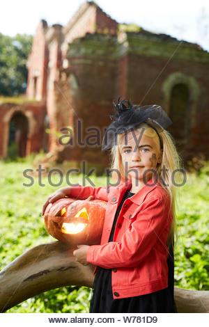 Portrait of cute little girl habillé en costume Halloween posant avec l'extérieur de la citrouille Banque D'Images
