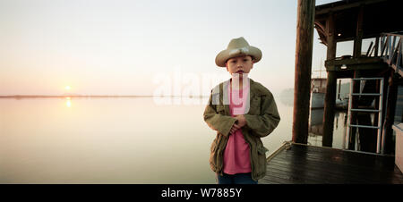 Boy standing on pier wearing cowboy hat Banque D'Images