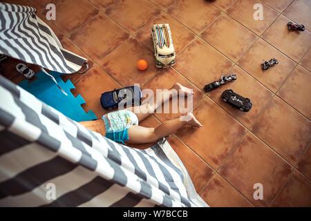 Bébé Garçon jouant à la maison, couché dans sa tente, vue du dessus sur le peu d'enfant espiègle, heureux de l'enfance insouciante