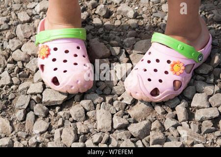 Girl in a pink children's beach, chaussures Crocs sur une route en pierre Banque D'Images