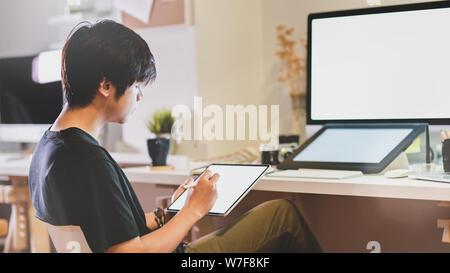 Vue rapprochée de la retouche photographe professionnel sur tablette dans son travail moderne