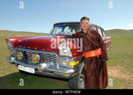 Un nomade mongol pose fièrement devant sa voiture russe vintage Banque D'Images