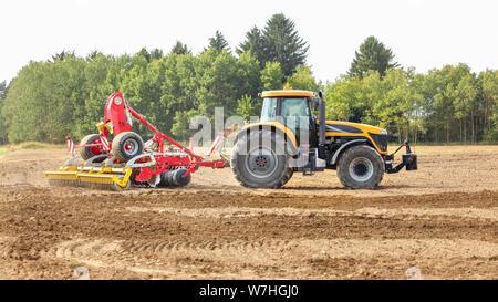 Tracteur jaune rouge tire sur les mécanisme de semis, arbres en arrière-plan. Banque D'Images