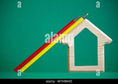 Une maison en bois du prince et plusieurs crayons de couleur isoler sur fond vert, un concept nouveau à l'école, selective focus Banque D'Images