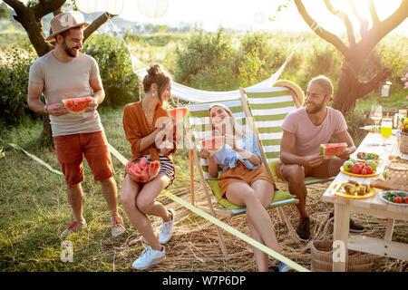 Un groupe de jeunes amis eating watermelon lors d'un repas festif dans le jardin joliment décorées sur un coucher de soleil Banque D'Images
