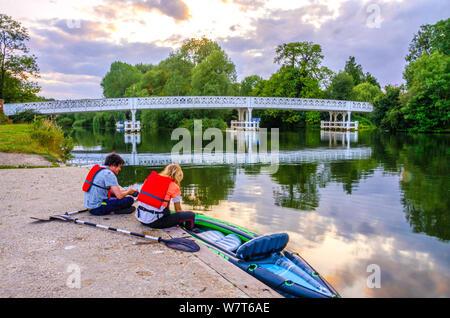 Un couple de canoéistes s'asseoir sur la rive de la Tamise en face de l'Whitchurch pont qui relie les villages de Whithcurch et Reading.