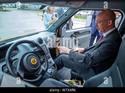 Wittenburg, Allemagne. 07Th Aug 2019. Christian Pegel (SPD), l'énergie et le ministre des Transports, de Mecklembourg-Poméranie occidentale, est assis sur le siège passager d'un 'street', un moteur électrique et van pour la Deutsche Post la livraison de colis personnel. Pegel peuvent en savoir plus sur l'utilisation de l'électromobilité au Deutsche Post DHL. Des 14 300 véhicules exploités par la Deutsche Post dans toute l'Allemagne, autour de 9 000 camionnettes de livraison sont à commande électrique. En plus de l'treetscooter', 3 000 e-bikes sont également en cours d'utilisation. Credit: Jens Büttner/dpa-Zentralbild/dpa/Alamy Live News Banque D'Images
