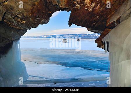 Voir à travers la roche de passage de véhicules stationnés sur la glace sur la surface du lac Baikal, Sibérie, Russie, mars 2012. Banque D'Images
