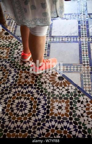 Femme avec néon formateurs debout sur le Palais Bahia 600x600 à Marrakech, Medina - Maroc Banque D'Images