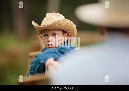 Jeune garçon portant un chapeau de cow-boy s'appuie sur la clôture à un ranch et écoute son père lui dire au sujet des chevaux. Banque D'Images