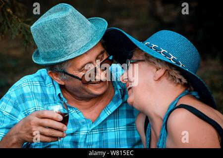 Happy senior couple kissing tandis que boire du vin ensemble sur un pique-nique dans le parc Banque D'Images