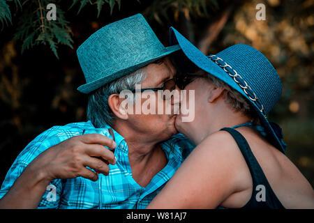 Senior couple kissing tandis que boire du vin ensemble sur un pique-nique dans le parc Banque D'Images