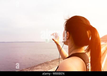 Sport femme debout sur la baie et l'eau potable après l'exécution