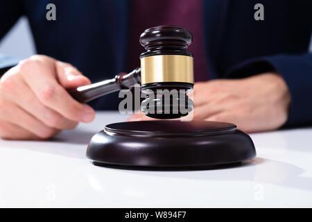 La main du juge de trouver le Gavel On Sounding Block Over White 24, dans la salle d'audience Banque D'Images