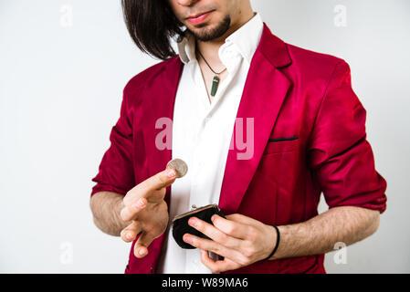 Un jeune homme prend la main des pièces à partir d'un petit sac à main d'acheter quelque chose. Banque D'Images