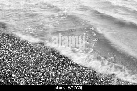 Plage de galets avec bébé surf Banque D'Images