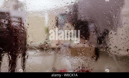 Gouttes de pluie sur la surface du panneau de verre fenêtre humide en saison des pluies. Résumé fond. Modèle naturel des gouttes isolées de l'extérieur de la ville floues dans Banque D'Images