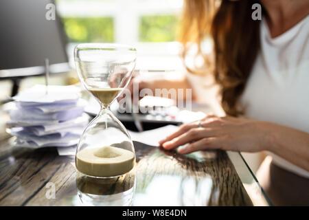 Close-up d'un sablier en face de Businesswoman Working in Office Banque D'Images