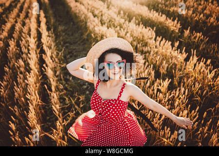 Femme en champ de blé. Old fashioned girl à chapeau de paille, robe rouge à pois.