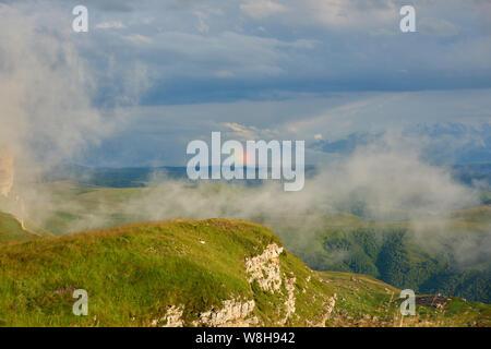 Arc-en-ciel sur une vallée de montagne avec du brouillard à l'avant-plan.