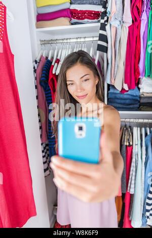Asian girl en tenant un smartphone de sa tenue mode selfies dans la chambre penderie. Femme à l'aide de styling app sur le téléphone pour prendre une photo de son nouveau magasin de vêtements à la maison ou d'essayage. Concept commercial.