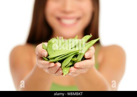 Woman holding fresh Asian les pois en mains libre isolé sur fond blanc. femme montrant poignée de gousses de pois mange-tout vert en creux des mains. Légumes régime sain concept. Banque D'Images