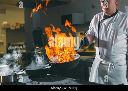 Chef, c'est en remuant les légumes dans les travaux sur la cuisine. Banque D'Images
