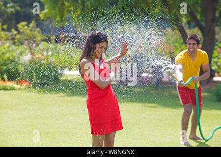 Petit ami pulvériser de l'eau sur sa petite amie avec un tuyau flexible dans un jardin Banque D'Images