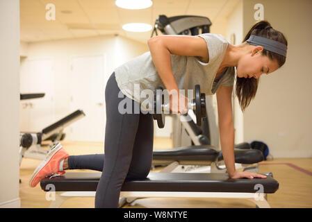 Salle de Sport fitness musculation haltères femme de levage des poids en-plus One-Arm rangée d'haltères. Femme fitness petite fille l'exercice piscine dans un centre de remise en forme. Belle forme de race caucasienne asiatique modèle. Banque D'Images