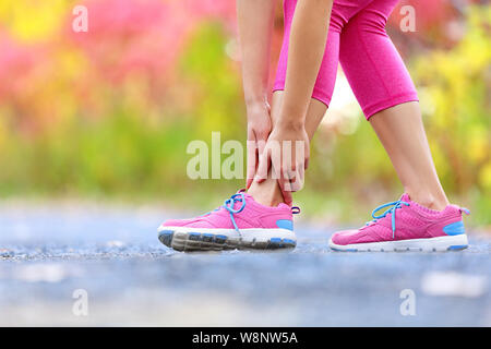 L'exécution de blessures sportives - twisted cheville cassée. Athlète féminin runner toucher pied dans la douleur à cause de l'entorse de cheville.