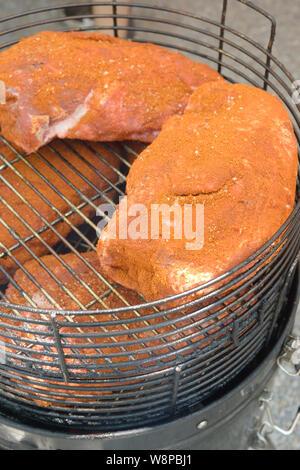 L'Italie, Lombardie, Crema, Food Street Festival, épaules de porc cuisson lentement sur un feu de barbecue Smokey Banque D'Images