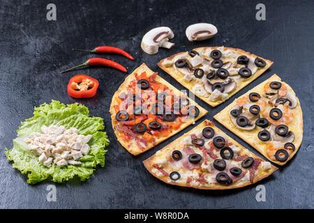 Assortiment de tranches de pizza. Margherita, pepperoni, fromage pizza quatre. Vue d'en haut. Différents types de pizza sur la table en bois texturé Banque D'Images