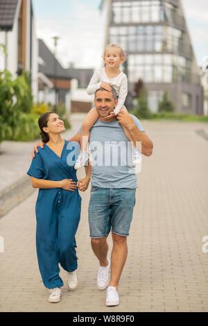 Strong man hugging aimant sa femme et fille d'avoir sur le cou Banque D'Images