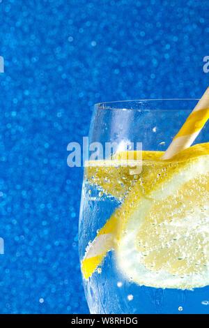 Des bulles de soude avec un cube de glace, d'une tranche de citron et une paille sur un fond bleu brillant Banque D'Images