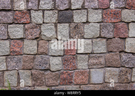 Des morceaux de briques pavés granit de cubes rouge gris rose noir, texture de fond. Les murs de maçonnerie de granit d'édifices anciens. Morceaux de granit Banque D'Images