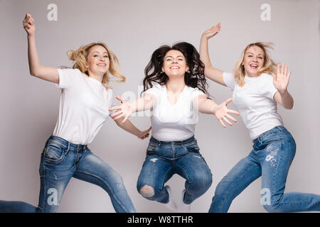 Trois amis dans les tenues de danse et de saut. Différents, mais de belles dames en jeans et t-shirts s'amuser et de sourire. Happy young Banque D'Images
