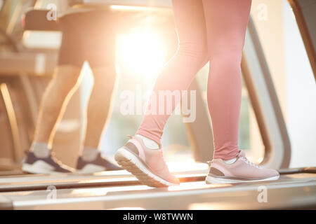 Arrière-plan de sports des gens courir sur des tapis roulants dans sport éclairée par la lumière du soleil, copy space