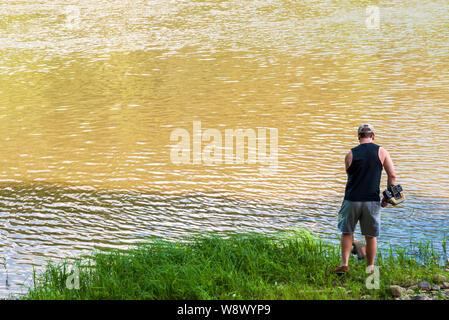 Un homme à l'aide d'une garniture à la lutte contre les mauvaises herbes à gazon whacker le long de la rivière Allegheny dans Warren comté en été, Althom, New York, USA Banque D'Images