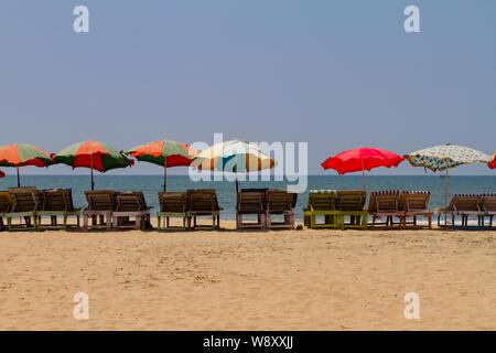 Rangée de chaises de terrasse de bois couverte avec parasols colorés sur la plage de Goa, en Inde. Fond d'été de la mer. Maison de modèle. Banque D'Images