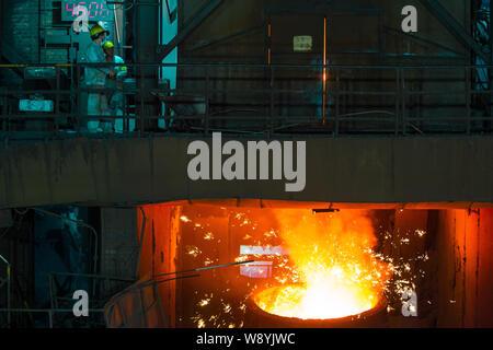 --FILE--regarder les travailleurs chinois de l'acier en fusion est versé dans un moule à une usine sidérurgique de la ville de Hangzhou, province de Zhejiang en Chine de l'Est, 5 août 2014. Banque D'Images