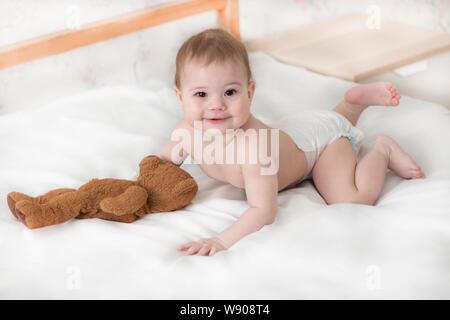 Cheerful baby boy girl dans une couche couché avec un ours en peluche. Mignon bébé dans une couche de ramper sur le lit, regarder dans l'appareil photo bébé avec un ours en peluche Banque D'Images