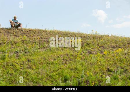 Un jeune homme est assis sur le dessus de la colline et regarde dans Téléphone. Le tourisme repose sur randonnée pédestre, vu avec la carte dans le navigateur. blooming colline verte, ciel bleu clair Banque D'Images
