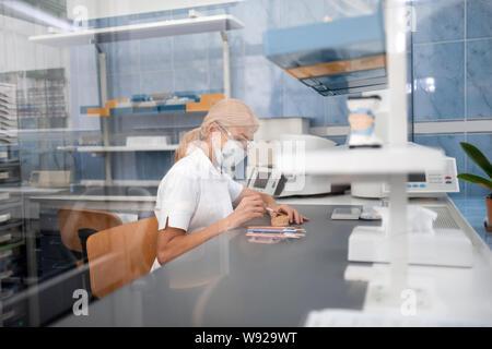 Technicien dentaire travaillant sur porcelaine prothèse dans son laboratoire. Banque D'Images