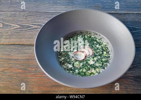 Vue de dessus de yummy soupe froide de tomates restant sur la table. Okroshka savoureux avec le kéfir, persil et radis servi dans le cafe en été. Délicieux repas pour le dîner. Concept de dîner et de l'alimentation. Banque D'Images