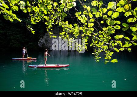 Mère et fils s'amusant sur le stand up paddle sur la magnifique rivière Idrijca à Most na Soci, Slovénie