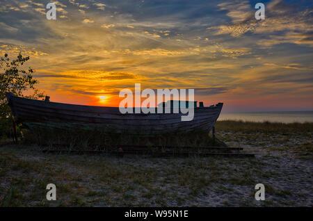 Ancien bateau de pêcheur en mer Baltique pendant le coucher du soleil Banque D'Images