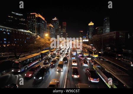 --FILE--vue de la nuit de masses de voitures et bus se déplaçant lentement au cours d'un embouteillage à Pékin, Chine, 23 décembre 2011. Le nombre de voitures immatriculées Banque D'Images