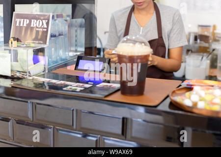 Caisse avec mise au point sélectionné barista femme travaillant derrière le comptoir bar. Banque D'Images